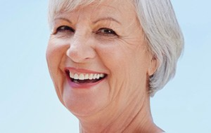 Senior woman with natural looking implant denture