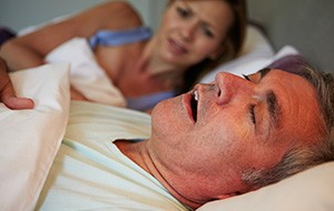 Frustrated woman looking at snoring man in bed