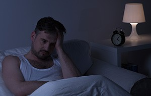 Frustrated man in bed holding head in hands