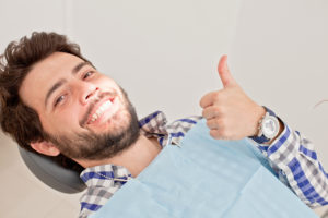 man in dentist chair thumbs up