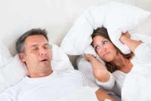 A woman closing her ears because her husband snores