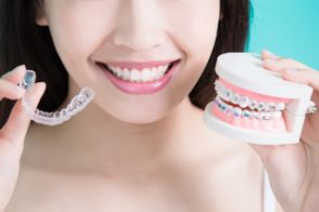 Woman holding Invisalign tray and braces in each hand
