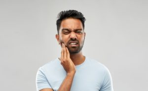 Man holding jaw in discomfort