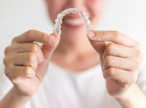 Smiling woman holding clear braces