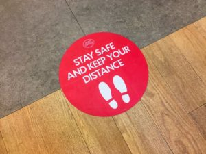 Red floor sign from Lincoln dentist encouraging social distancing in COVID-19