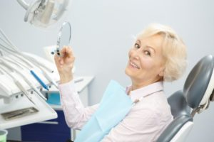 Woman smiles after getting dental implants in Lincoln