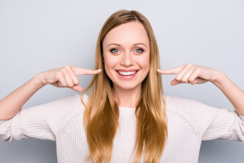 Woman pointing to her aesthetically pleasing smile